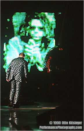 Live concert photo of Bono with photo of Michael Hutchence